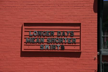 """Longer Days means Shorter Skirts"" sign in Berkeley"