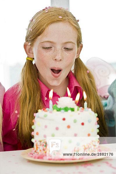 Mdchen Ausblasen Kerzen auf einem Geburtstagskuchen