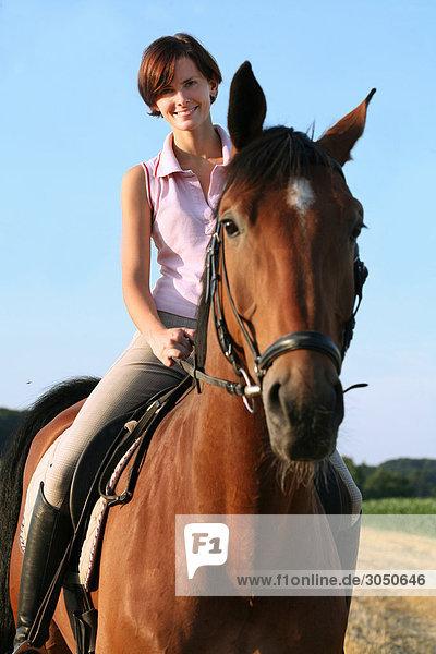 Junge Frau auf Pferd sitzend Oberer Ausschnitt