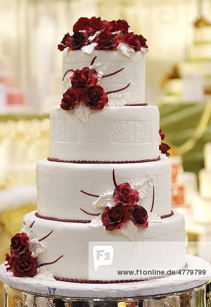 Mehrstckige Hochzeitstorte geschmckt mit roten Rosen