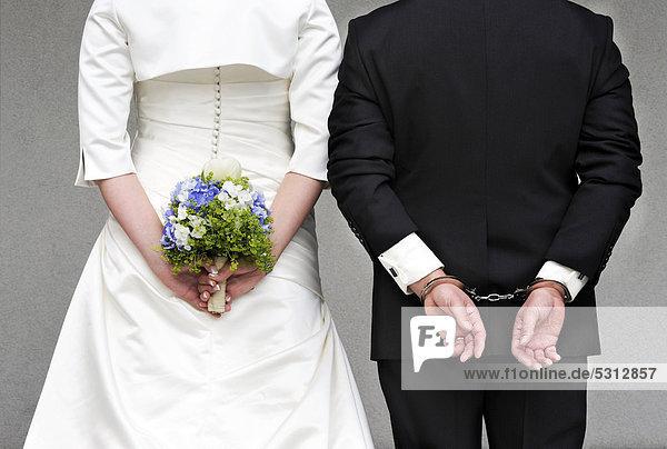 Hochzeitspaar von hinten Braut hlt Brautstrau Brutigam in Handschellen iblset02034420