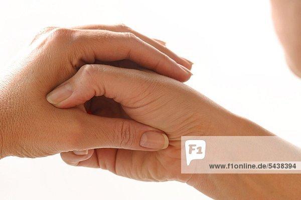 nahdetail junge frau massiert sich den handballen finger akupressur handflache gegen nierenschmerzen blasenschwache fur die ausseren geschlechtsorgane