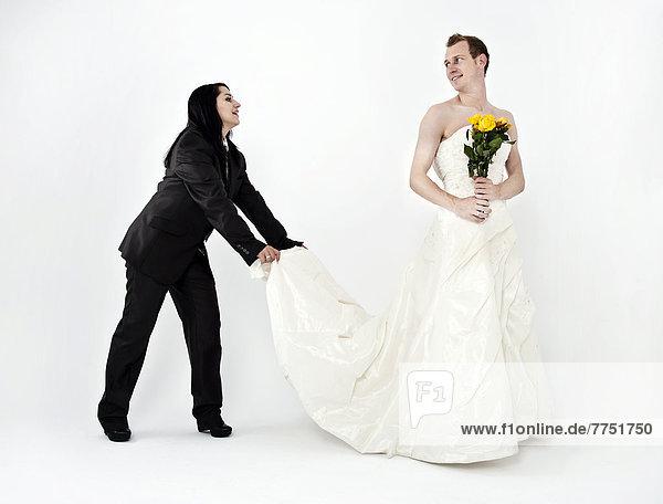 Frau in Anzug hlt Brutigam in Hochzeitskleid die Schleppe Alter 30 Jahre mnnlichAnzugBlumen