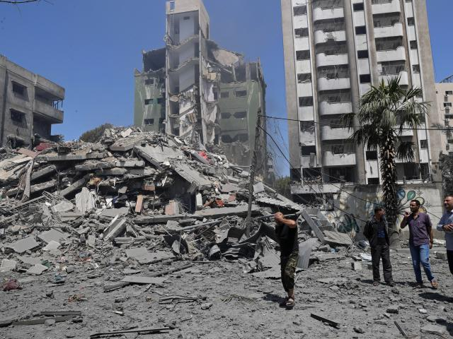 People inspect the rubble of a destroyed residential building that was hit by an Israeli airstrike, in Gaza City, Sunday, May 16, 2021. (AP Photo/Adel Hana)