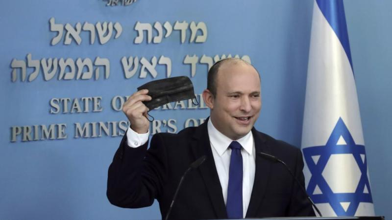 Israeli Prime Minister Naftali Bennett holds up a face mask as he delivers a statement on the coronavirus situation, in Jerusalem Wednesday, July 14, 2021.  (AP Photo/Maya Alleruzzo)