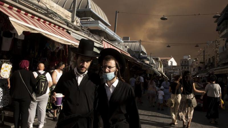 Ultra-Orthodox Jews stroll through the Machane Yehuda market under a sky darkened by nearby wildfires, in Jerusalem, Sunday, Aug. 15, 2021.(AP Photo/Maya Alleruzzo)