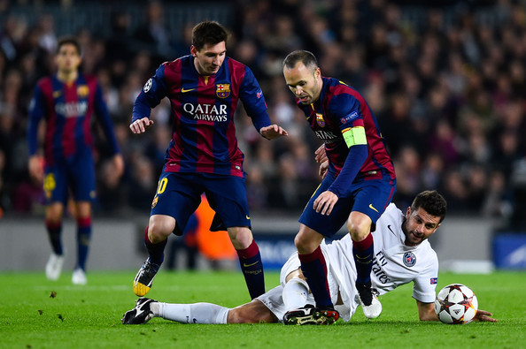 Thiago Motta of Paris Saint-Germain FC competes for the ball with Lionel Messi (L) and Andres Iniesta of FC Barcelona during the UEFA Champions League group F match between FC Barcelona and Paris Saint-Germanin FC at Camp Nou Stadium on December 10, 2014 in Barcelona, Spain.