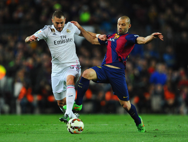 Karim Benzema of Real Madrid CF battles with Javier Mascherano of Barcelona during the La Liga match between FC Barcelona and Real Madrid CF at Camp Nou on March 22, 2015 in Barcelona, Spain.