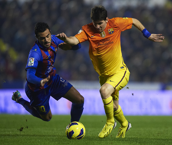 Vicente Iborra (L) of Levante competes for the ball with Lionel Messi of Barcelona during the la Liga match between Levante UD and FC Barcelona at Ciutat de Valencia on November 25, 2012 in Valencia, Spain.