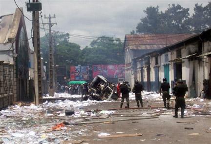 Les forces de sécurité de l'État, le 27 janvier 2009, devant un bâtiment appartenant à la famille du président malgache, Marc Ravalomanana, pillé et brûlé la veille, à Antananarivo.(Photo : AFP)
