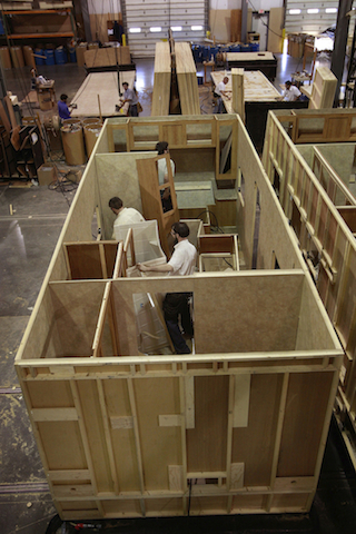 Workers construct a modular structure in a manufacturing facility. ©iStock.com/EdStock
