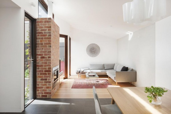 Living room with fireplace from recycled bricks as a feature.Lower ceiling at seating area, higher ceiling at doors area.Balanced natural light throughout, Image Courtesy © STEFFEN WELSCH ARCHITECTS