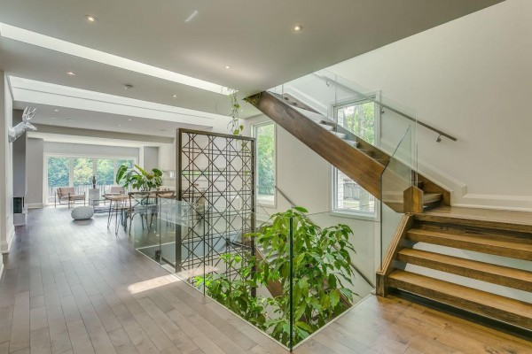 """Interior View from main Floor. This home tailors a complex relationship of mass-to-void by interconnecting the Garden from the basement to the second floor through a Void."""" The Void shares an internal journey through the building"""", Image Courtesy © Navid Aali"""