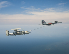 An E-2C test aircraft assigned to Air Test and Evaluation Squadron (VX) 20 conducts an aerial refueling dry-plug engagement with an F/A-18.