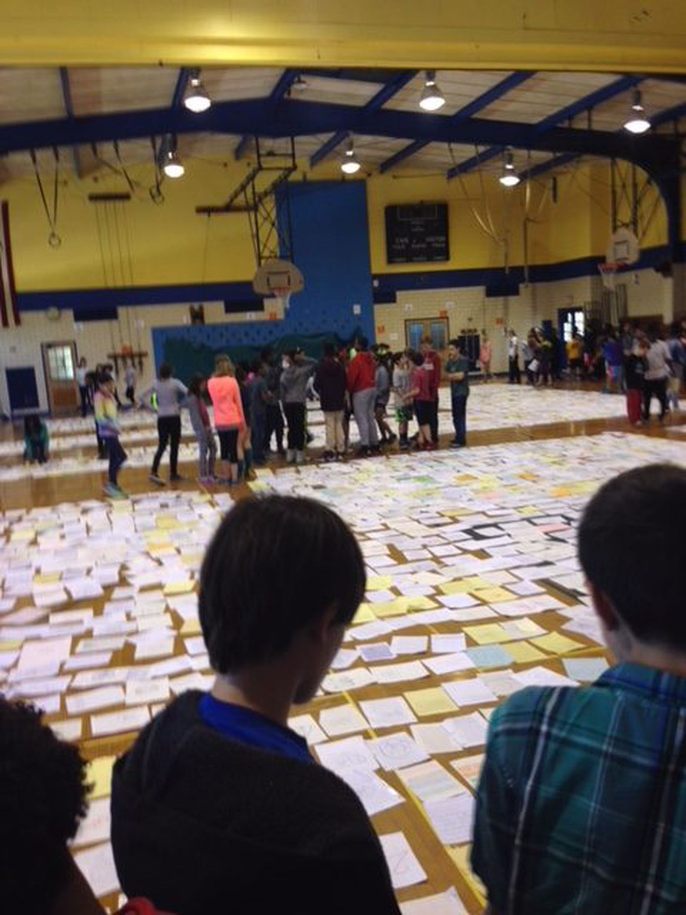 Elkins Park School teacher Lise Marlowe's students spread out on the gym floor the stick figure drawings they made to represent Holocaust victims. After 20 years, her classes are only up to 1.3 million victims.