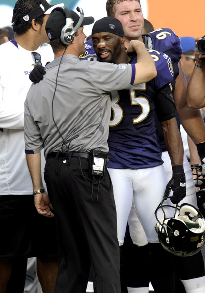 Coach John Harbaugh of the Baltimore Ravens hugs wide receiver Derrick Mason #85 after play against the Miami Dolphins during their AFC Wild Card Game at Dolphins Stadium on January 4, 2009 in Miami, Floirda.  (Photo by Al Messerschmidt/Getty Images) *** Local Caption *** John Harbaugh;Derrick Mason
