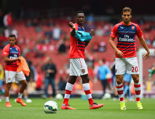 Danny Welbeck of Arsenal puts on his bib as he warms up with Mathieu Flamini of Arsenal during the Barclays Premier League match between Arsenal and Manchester City at Emirates Stadium on September 13, 2014 in London, England.