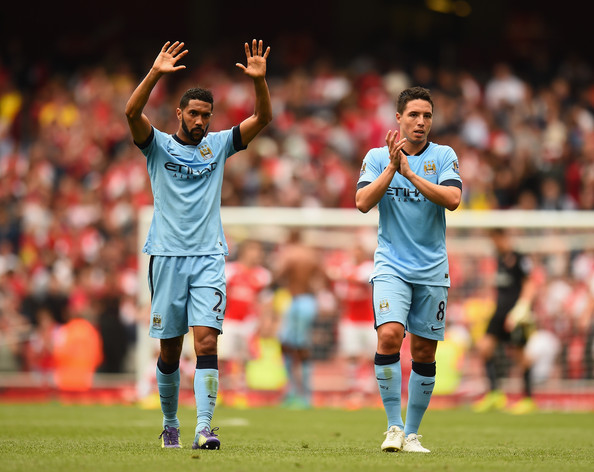 Gael Clichy and Samir Nasri of Manchester City acknowledge the crowd after the Barclays Premier League match between Arsenal and Manchester City at Emirates Stadium on September 13, 2014 in London, England.