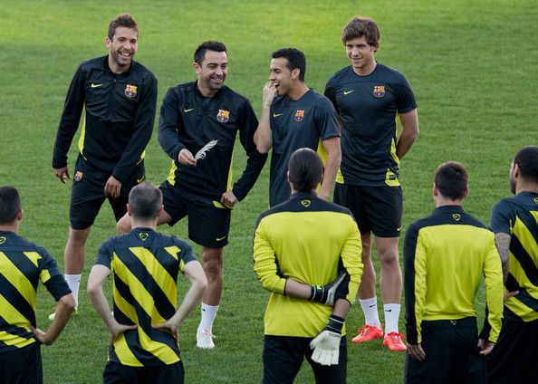 Xavi Hernandez of FC Barcelona jokes holding a feather in the middle of his team during the training session the day before the UEFA Champions League Quarter-final match between Atletico de Madrid and FC Barcelona at Vicente Calderon Stadium on April 8, 2014 in Madrid, Spain.