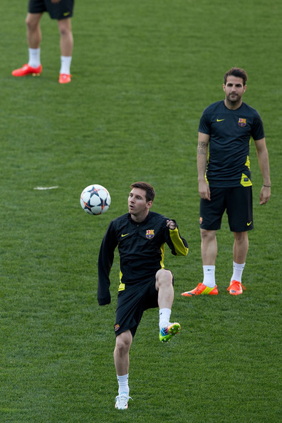 Lionel Messi (L) of FC Barcelona controls the ball as his teammate Cesc Fabregas (R) looks him  during the training session the day before the UEFA Champions League Quarter-final match between Atletico de Madrid and FC Barcelona at Vicente Calderon Stadium on April 8, 2014 in Madrid, Spain.