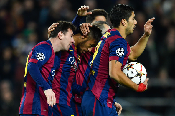 Lionel Messi (L) of FC Barcelona celebrates after scoringm their first goal during the UEFA Champions League group F match between FC Barcelona and Paris Saint-Germanin FC at Camp Nou Stadium on December 10, 2014 in Barcelona, Spain.