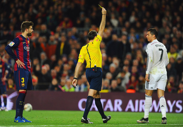 Referee Antonio Miguel Mateu Lahoz shows a yellow card to Cristiano Ronaldo of Real Madrid CF during the La Liga match between FC Barcelona and Real Madrid CF at Camp Nou on March 22, 2015 in Barcelona, Spain.