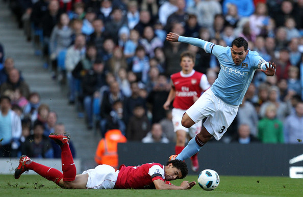 Carlos Tevez of City is brought down by Denilson of Arsenal during the Barclays Premier League match between Manchester City and Arsenal at City of Manchester Stadium on October 24, 2010 in Manchester, England.