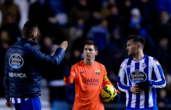 Lionel Messi (2ndL) of FC Barcelona shake hands with Haris Medunjanin (L) of RC Deportivo La Coruna as he holds the ball after his hat-trick at the end of the La Liga match between RC Deportivo La Coruna and FC Barcelona at Riazor Stadium on January 18, 2015 in La Coruna, Spain.