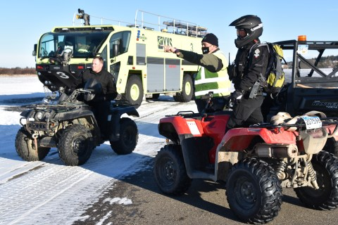 People gather on quads and side-by-sides at the Prince George airport as they prepare to get a moose of the property