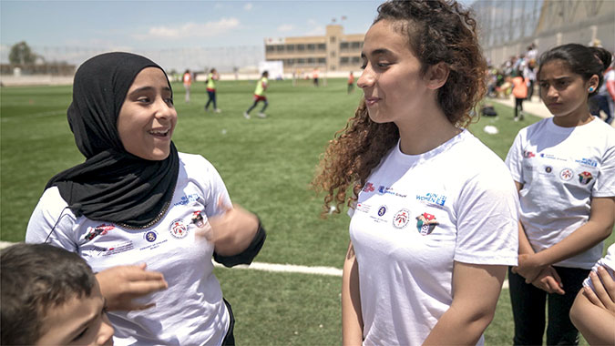 Syrian refugees and Jordanian girls build positive relationships during a mixed-nationality football camp in Jordan. Photo: UN Women/Christopher Herwig