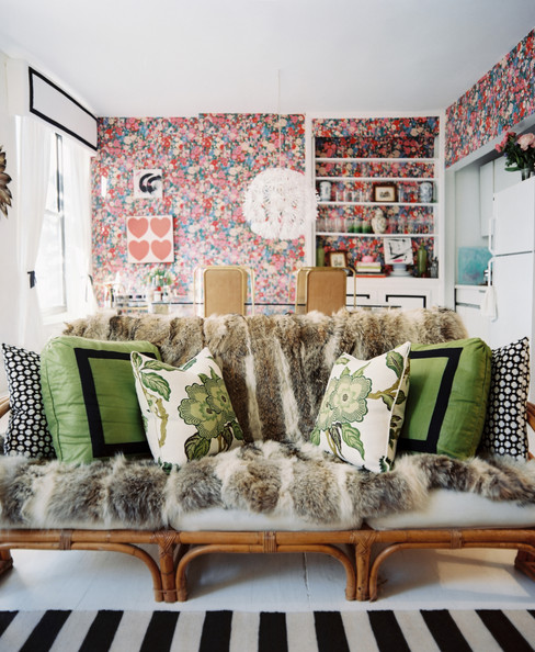 Bohemian Living Room - A vintage bamboo couch covered with a fur throw and green pillows