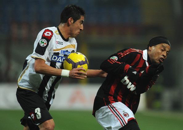 Ronaldo de Assis Moreira Gaucho Ronaldinho of AC Milan is challenged by Mauricio Isla  of Udinese Calcio during the Serie A match between AC Milan and Udinese Calcio at Stadio Giuseppe Meazza on February 12, 2010 in Milan, Italy.