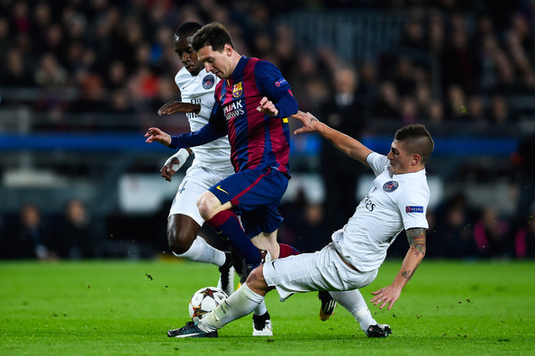 Lionel Messi of FC Barcelona competes for the ball with Blaise Matuidi (L) and Marco Verratti of Paris Saint-Germain FC during his team's first goal of FC Barcelona  during the UEFA Champions League group F match between FC Barcelona and Paris Saint-Germanin FC at Camp Nou Stadium on December 10, 2014 in Barcelona, Spain.