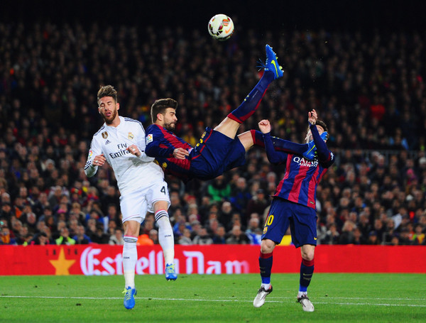 Lionel Messi of Barcelona looks on as Gerard Pique of Barcelona attempts an overhead kick under challenge from Sergio Ramos of Real Madrid CF during the La Liga match between FC Barcelona and Real Madrid CF at Camp Nou on March 22, 2015 in Barcelona, Spain.