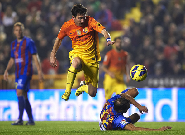 Lionel Messi of Barcelona is tackled by Juanfran of Levante during the la Liga match between Levante UD and FC Barcelona at Ciutat de Valencia on November 25, 2012 in Valencia, Spain.
