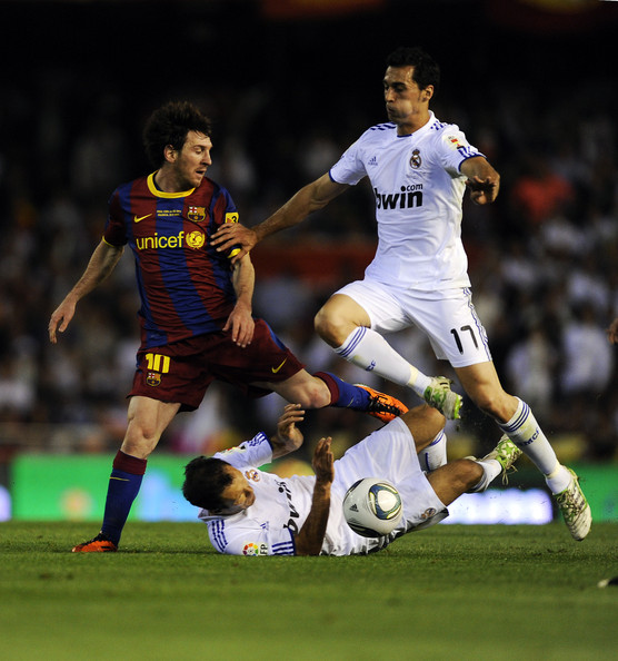 Lionel Messi of FC Barcelona (L) holds a challenge by Ricardo Carvalho (C) and Alvaro Arbeloa  of Real Madrid (R) during the Copa del Rey Final between Real Madrid and Barcelona at Estadio Mestalla on April 20, 2011 in Valencia, Spain.