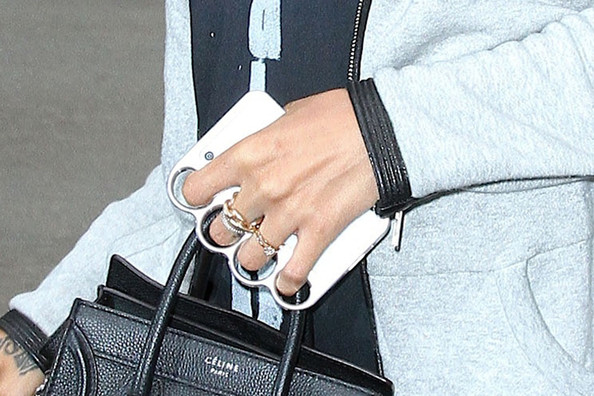 Rihanna shows off her brass knuckle style iPhone case while arriving at an office building in New York City. Rihanna can also be seen carrying a Celine Paris bag.