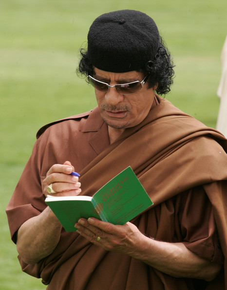 "Libyan leader Muammar Qadaffi looks at a Russian language edition of his book ""The Green Book"" during his meeting with Russian President Vladimir Putin April 17, 2008 in Tripoli, Libya. Putin is in Libya for a two-day official visit to rebuild Russian-Libyan relations."