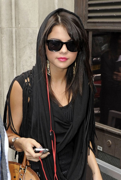 Selena Gomez Selena Gomez uses her scarf as a hood while leaving the Radio One studios.