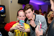 Musician Shawn Mendes poses with a fan backstage at the Q102's Jingle Ball 2014 at Wells Fargo Center on December 10, 2014 in Philadelphia, Pennsylvania.