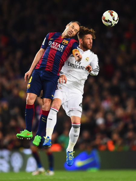 Andres Iniesta of Barcelona jumps with Sergio Ramos of Real Madrid CF during the La Liga match between FC Barcelona and Real Madrid CF at Camp Nou on March 22, 2015 in Barcelona, Spain.