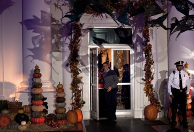 U.S. President Barack Obama (C) walks out of the White House to greet trick or treaters October 31, 2010 in Washington, DC. The Obama's greeted children and military families at the North Portico to celebrate Halloween and to trick or treat across the North Lawn.