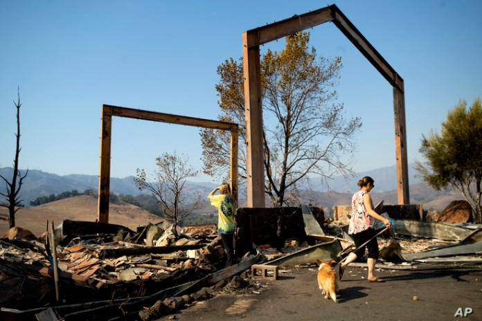 Stephanie LaFranchi, right, and Ashley LaFranchi examine the remains of their family's Oak Ridge Angus ranch, leveled by a wildfire called Kincade Fire, in Calistoga, Calif., Oct. 28, 2019.