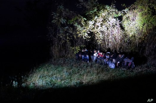 In this photo taken Saturday, Nov. 9, 2019, Bosnian border police officers guard migrants after making the illegal crossing…