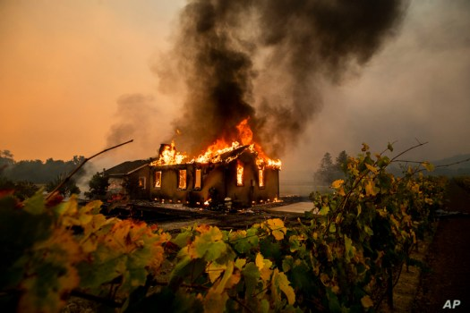 Vines surround a burning building as the Kincade Fire burns through the Jimtown community of unincorporated Sonoma County, California, Oct. 24, 2019.