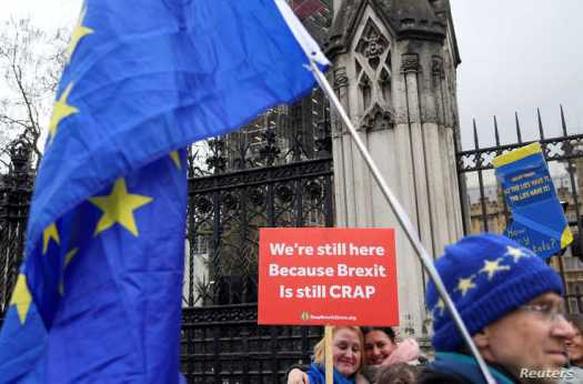 Anti-Brexit demonstrators hold signs outside the Houses of Parliament in London, Britain, Dec. 17, 2019.