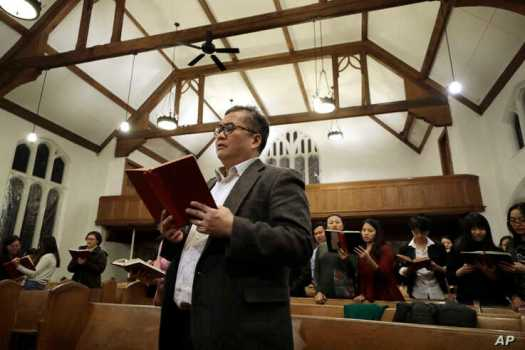 In this Sunday, Feb. 16, 2020, photo Baptist Pastor Clifford Maung, front, an immigrant from Myanmar, also known as Burma,…