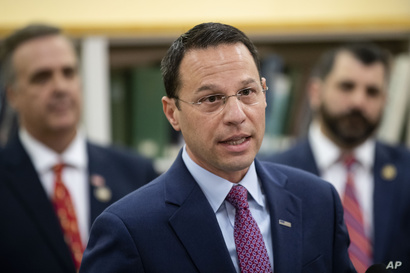 Pennsylvania Attorney General Josh Shapiro, center, accompanied by Rep. Jim Gregory, R-Blair, left, and Rep. Mark Rozzi, D…