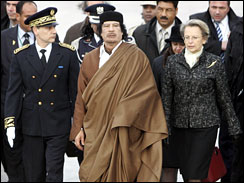 Lybian leader Moammar Gadhafi, center, reviews an honor guard with French Interior Minister Michele Alliot Marie, right, on his arrival at Paris Orly airport, Monday Dec. 10, 2007.