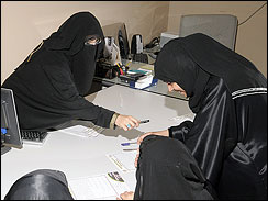 Khadra al-Mubarak, left, showing potential contestants brochures of the _Miss Beautiful Morals_ contest at her office in Safwa in the eastern province, Saudi Arabia, Tuesday, May 5, 2009.